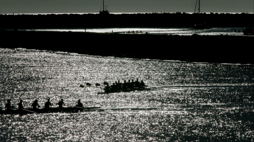 LOS ANGELES, CALIF. - MAR. 29, 2017. Crews row boats through the shimmering waters of Marina Del R