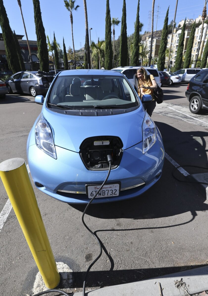 Angie Vorhies leaves her Nissan Leaf electric vehicle charging station as she heads for shopping at a mall Wednesday, Nov. 13, 2013, in San Diego. (AP Photo/Lenny Ignelzi)