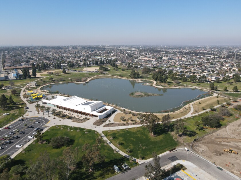 A drone shot shows an overhead view of one of the lakes at Magic Johnson Park surrounded by newly planted terrain