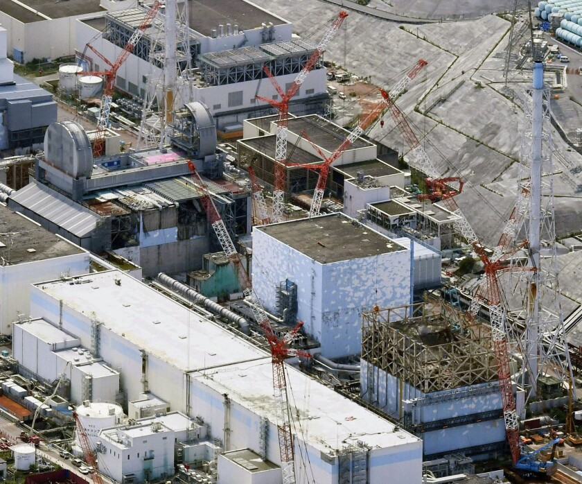FILE - This Sept. 4, 2017, aerial file photo shows Fukushima Dai-ichi nuclear power plant reactors, from bottom at right, Unit 1, Unit 2 and Unit 3, in Okuma town, Fukushima prefecture, northeastern Japan. The head of the wrecked Fukushima nuclear plant said Tuesday, March 2, 2021 there's no need to extend the current target to finish its decommissioning in 30-40 years despite uncertainties about melted fuel inside the plant's three reactors. (Daisuke Suzuki/Kyodo News via AP, File)