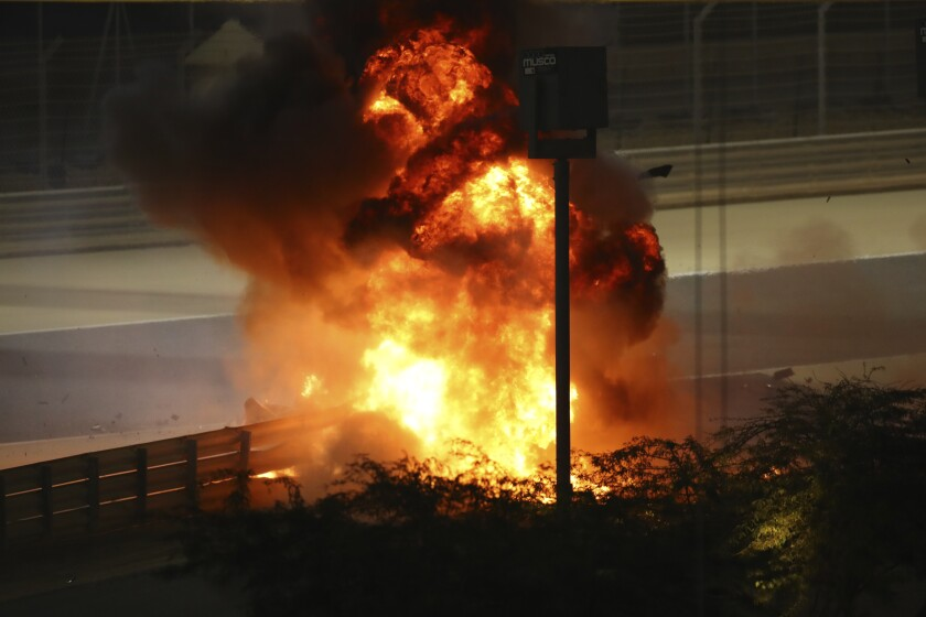 Flames seen from the crash scene after Haas driver Romain Grosjean of France crashed out at the start of the race during the Formula One race in Bahrain International Circuit in Sakhir, Bahrain, Sunday, Nov. 29, 2020. (Brynn Lennon, Pool via AP)