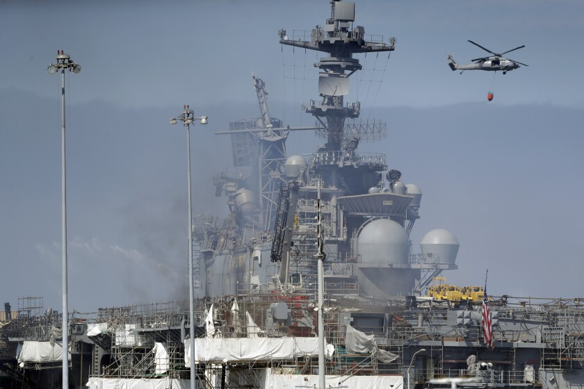 A helicopter carrying water passes the USS Bonhomme Richard, Tuesday, July 14, 2020, in San Diego. The battle to save the ship from a ravaging fire entered a third day in San Diego Bay on Tuesday with indications that the situation aboard the amphibious assault ship was improving. The U.S. Navy said in a statement late Monday that firefighters were making significant progress with the assistance of water drops by helicopters. (AP Photo/Gregory Bull)