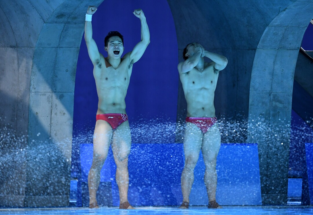 Two Chinese divers celebrate at poolside