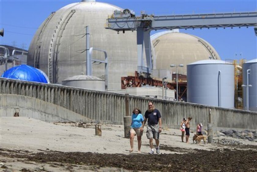 FILE - This file photo taken June 30, 2011, shows beach-goers walking on the sand near the San Onofre nuclear power plant in San Clemente , Calif. The utility that runs California's San Onofre nuclear plant misled federal regulators about equipment and design changes that are the likely cause of problems with tubing that carries radioactive water, a report commissioned by an environmental group claimed Tuesday March 27,2012. (AP Photo, Lenny Ignelzi, File)