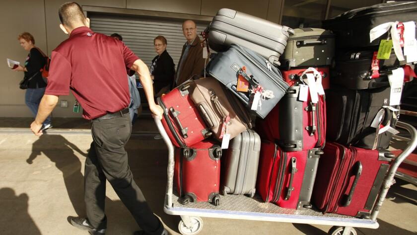 A baggage handler hauls a load at LAX.