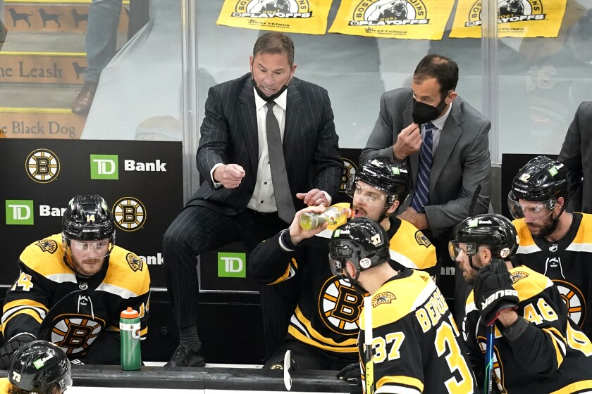 Boston Bruins head coach Bruce Cassidy, center, instructs his team during a timeout in the third period of Game 5 against the New York Islanders during an NHL hockey second-round playoff series, Monday, June 7, 2021, in Boston. (AP Photo/Elise Amendola)
