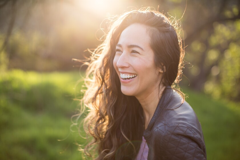 Marisa Quintanilla Griffeth smiles as the sun glows behind her.