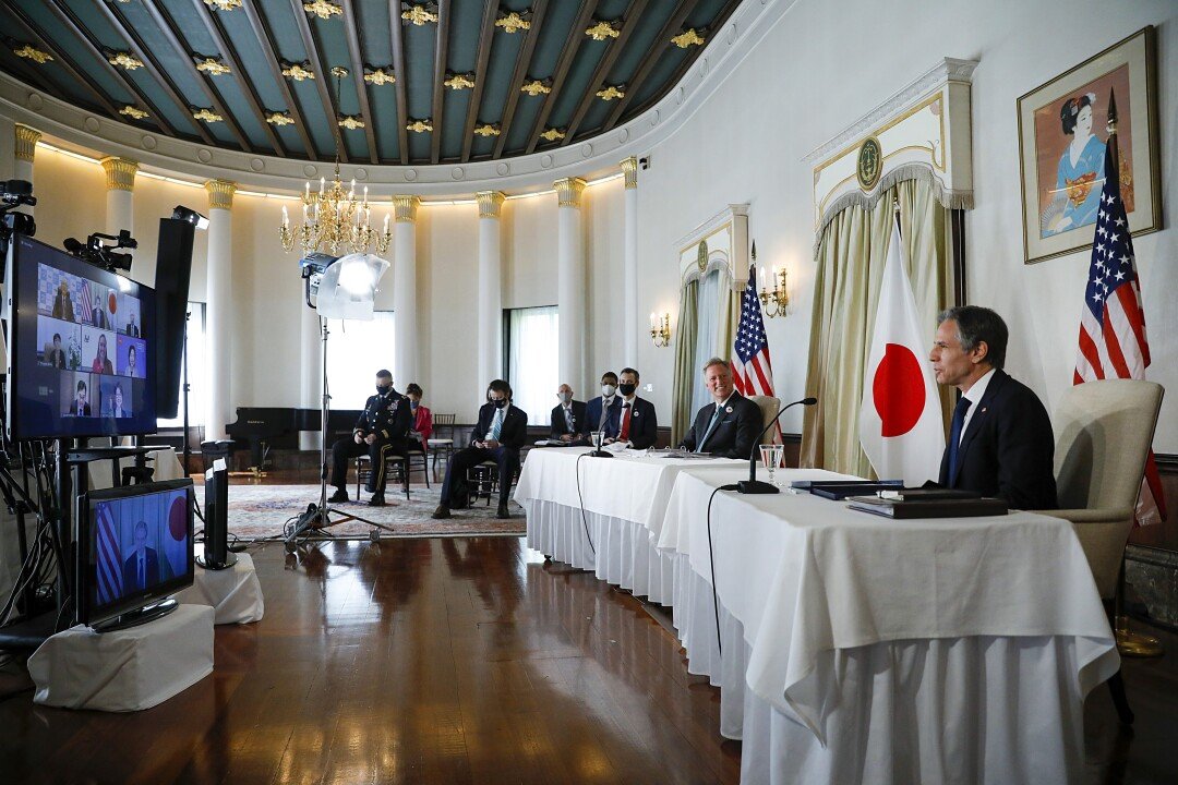 Secretary of State Antony J. Blinken, right, and other officials are seated apart, with U.S. and Japanese flags behind them