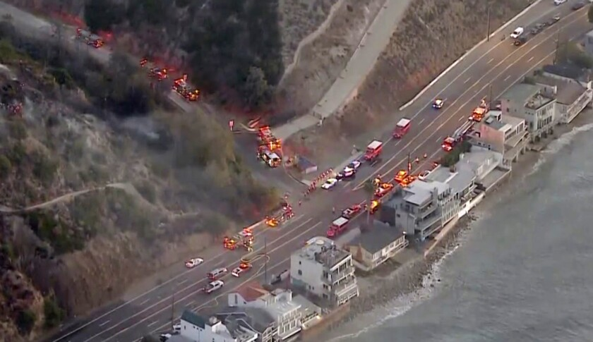 Firefighting crews mass near a small brush fire that broke out before dawn Friday in Malibu.