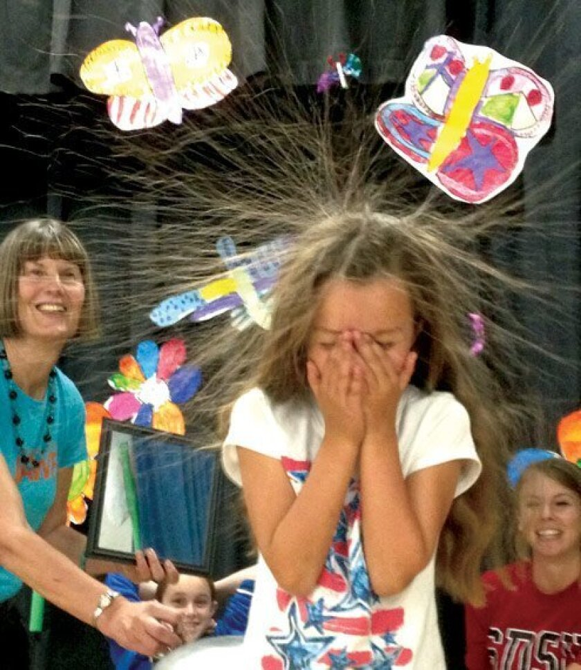 First-grader Sophia Ford and third-grade teacher Joan Boyle demonstrate static electricity. Courtesy Photos