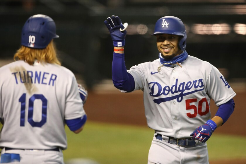 PHOENIX, ARIZONA - AUGUST 02: Mookie Betts #50 of the Los Angeles Dodgers celebrates with Justin Turner #10 after Betts hit a solo home run against the Arizona Diamondbacks during the fifth inning of the MLB game at Chase Field on August 02, 2020 in Phoenix, Arizona. (Photo by Christian Petersen/Getty Images)