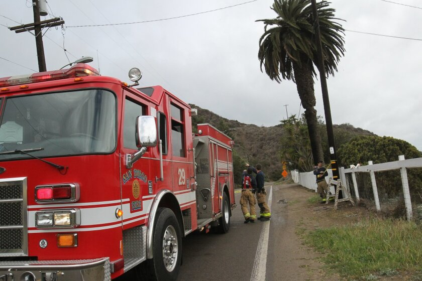 Firefighters cordon off an area of Monument Road in the Tijuana River Valley Friday after a large tree branch blew into power lines and downed them.
