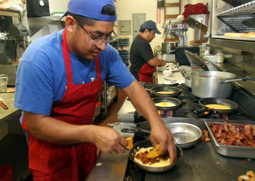 Cooks Gonzalo Diaz, left, and Luis Angelino working in the kitchen at St. Germain's restaurant Wednesday.