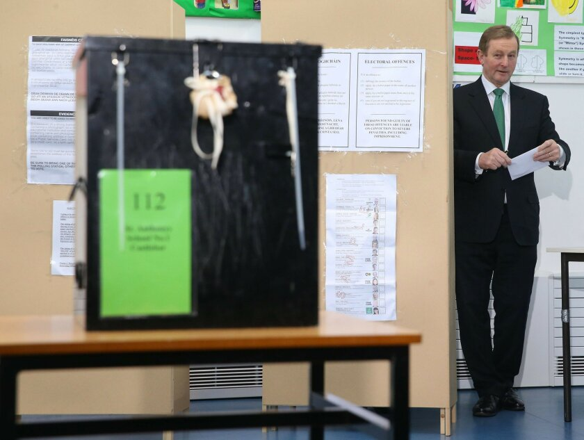 Ireland's Prime Minister Enda Kenny prepares to cast his vote at a polling station at St Anthony's School in Castlebar, Ireland, Friday Feb. 26, 2016. Ireland's voters were deciding Friday who should lead their economically rebounding nation for the next five years, with polls suggesting the outcome could be a hung parliament. (Brian Lawless/PA via AP) UNITED KINGDOM OUT