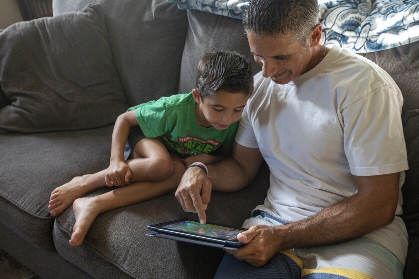 Jon Hatami plays a game with Jon Jr., 7, at home in Santa Clarita Valley.