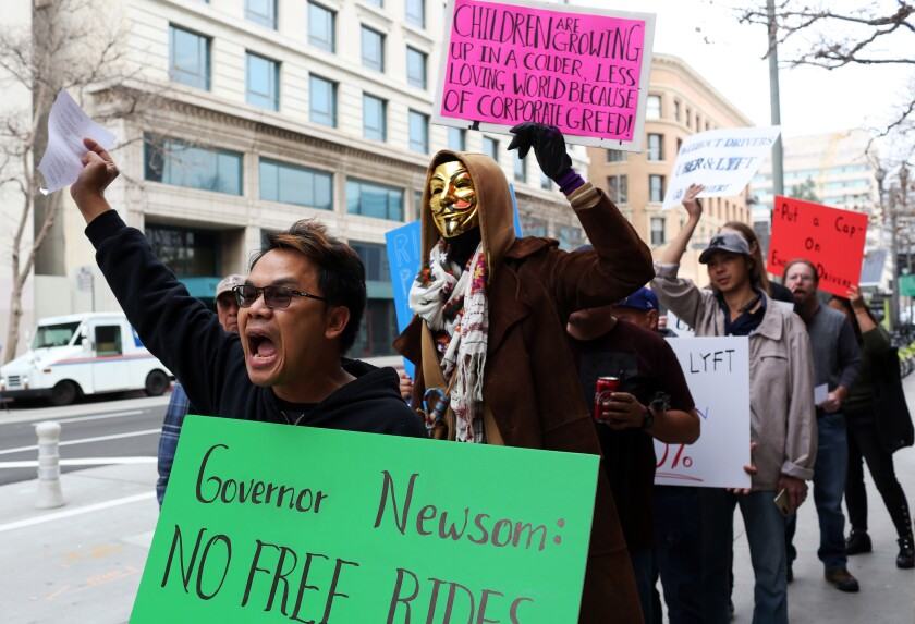 """Protesters carry signs and march on a city street. One sign says """"Governor Newsom: No free rides."""""""