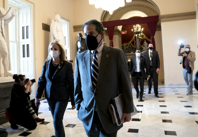 A woman and a man in face masks walk in a hallway.