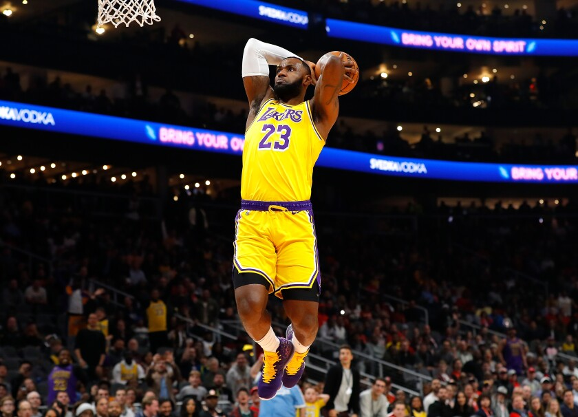 Lakers star LeBron James dunks during the first half of a 101-96 victory over the Atlanta Hawks on Sunday.