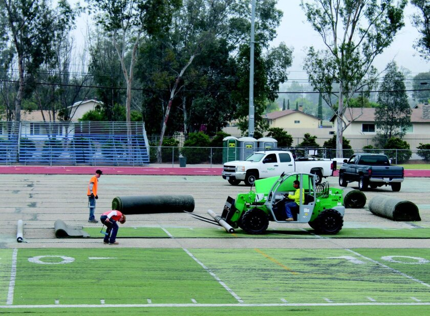 Workers pull and roll old turf at the high school field.