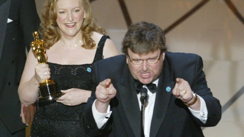 """Film director Michael Moore makes an anti-war statement as he accepts his Oscar for """"Bowling for Columbine"""" at the 75th Annual Academy Awards in Hollywood on March 23, 2003."""