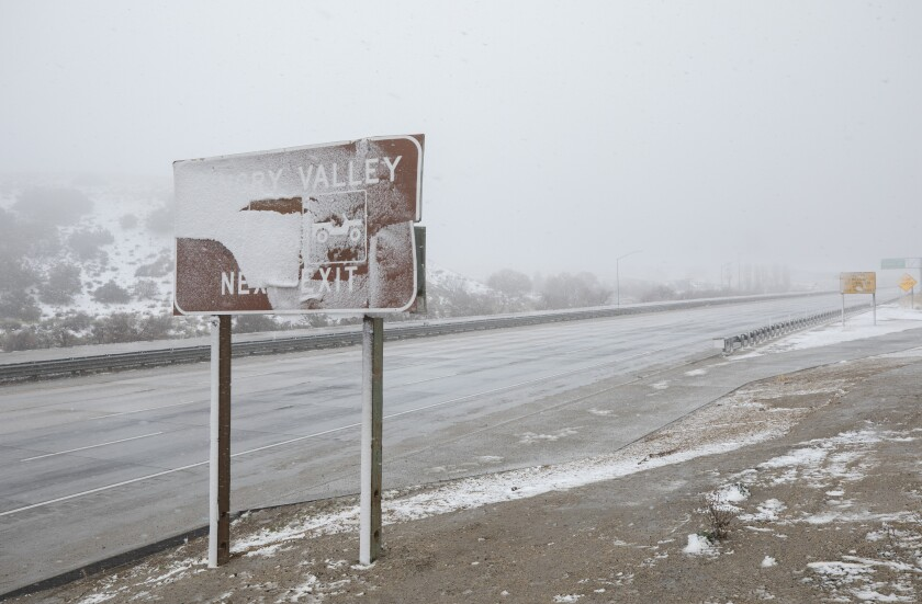 A lonely wintry and windblown highway with no cars