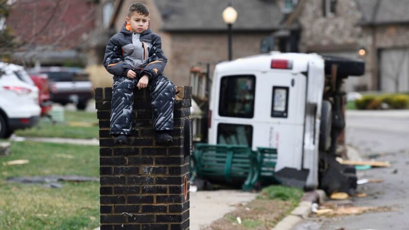 Gio Rodriguez, 8, sits outside his home as his parents clean up debris on Feb. 25, 2018, after a storm hit in the Farmington subdivision in Clarksville, Tenn.