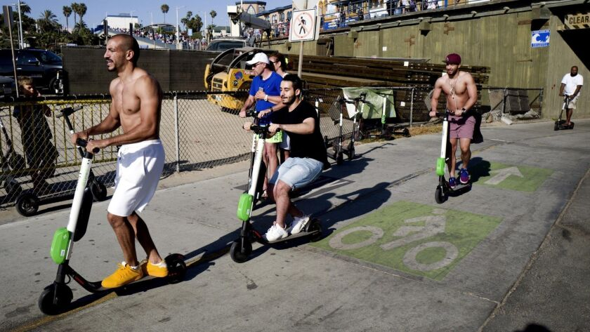 In this July 1, 2018 photo people ride Lime and Bird scooters along the strand in Santa Monica, Cali