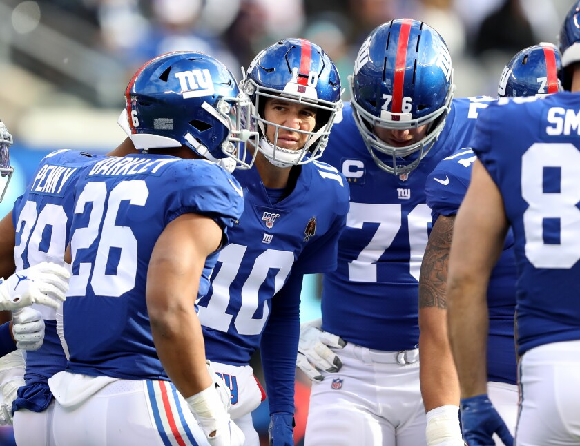 New York Giants quarterback Eli Manning huddles with his teammates during a win over the Miami Dolphins on Sunday.