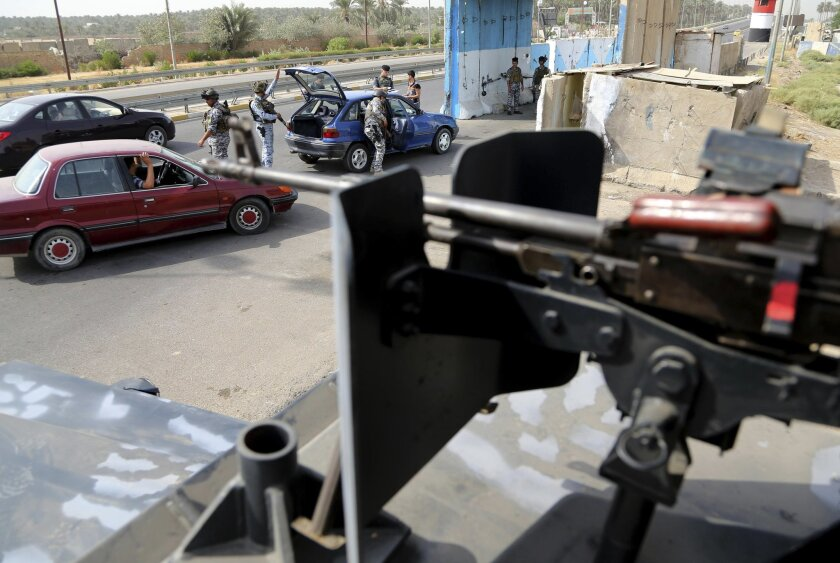 Iraqi federal policemen search a car at a checkpoint in Baghdad, Iraq, Saturday, Oct. 11, 2014. On the western edge of Iraq's capital, Islamic State group militants battle government forces and exchange mortar fire, only adding to the sense of siege in Baghdad despite airstrikes by a U.S.-led coalition. Military experts say the Sunni militants, won't be able to fight through both government forces and Shiite militias now massed around the capital, It does, however, put them in a position to wreak havoc in Iraq's biggest city, with its suicide attacks and other assaults. (AP Photo/Karim Kadim)