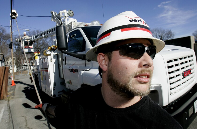 Verizon Utility worker Brian Roop pulls a cable as he and co-worker Steve Hammond install fiber-optic cable in Virginia.