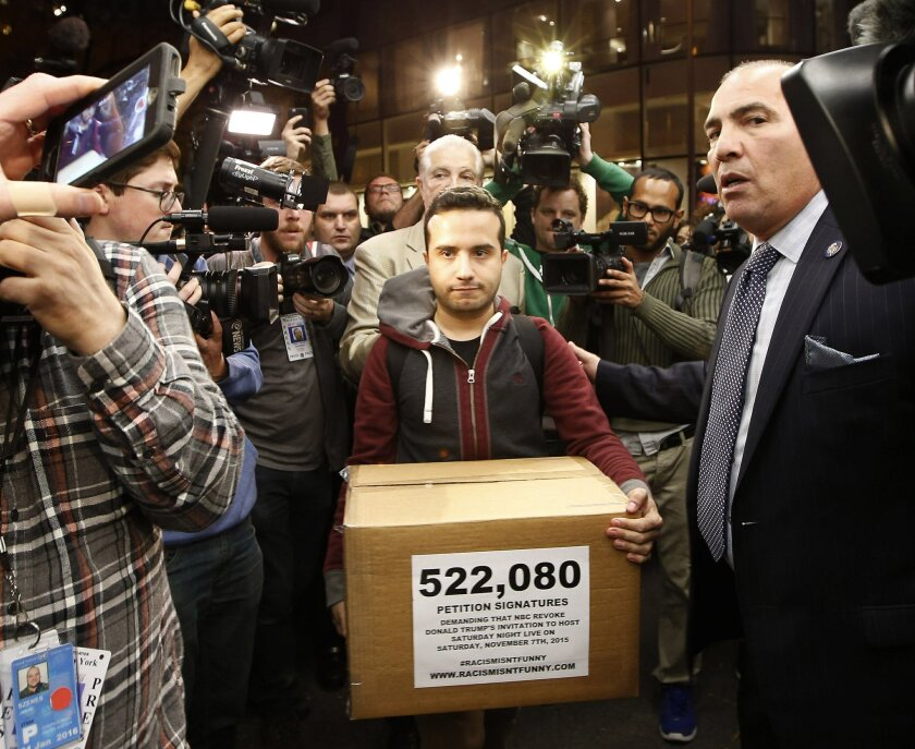 "Juan Escalante, campaign manager for the immigration reform group America's Voice, carries a box he claims contains over half a million petition signatures demanding that NBC revoke the invitation for Republican presidential candidate Donald Trump to be a guest-host on this weekend's ""Saturday Nigh"