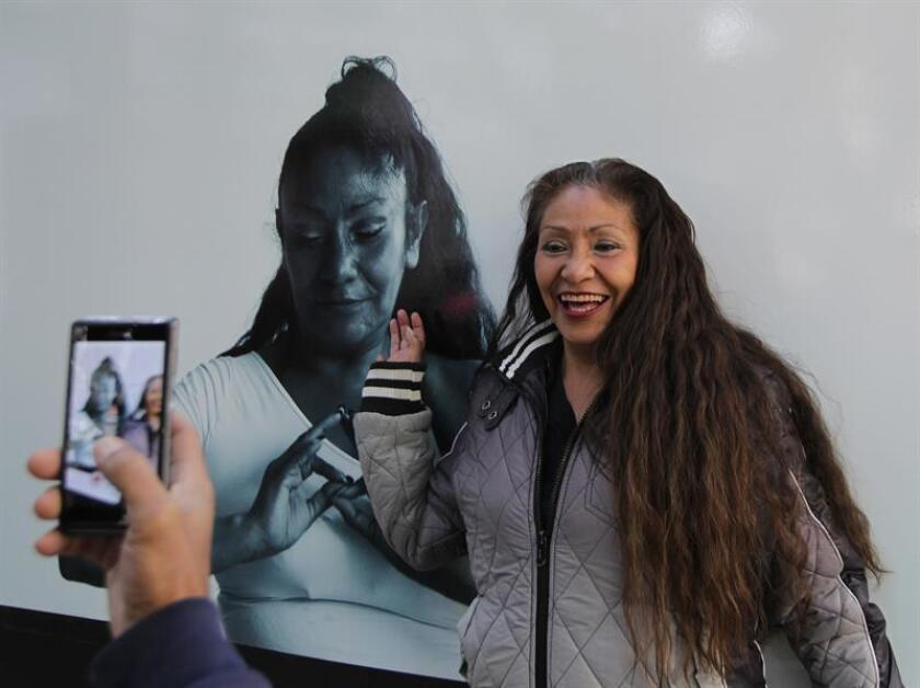 """La exinterna Maria S posa hoy, martes 16 de enero de 2018, junto a una de sus fotografías que hace parte de la muestra """"Reflejos de la Reinserción Social"""" expuesta en Ciudad de México (México). EFE"""