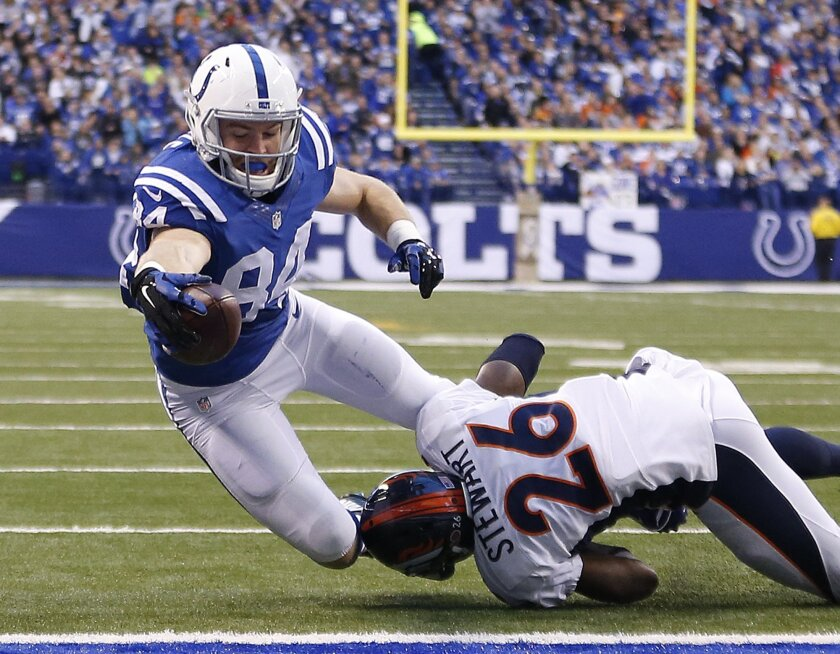Indianapolis Colts' Jack Doyle (84) dives for a three yard touchdown reception while being tackled by Denver Broncos' Darian Stewart (26) during the first half of an NFL football game, Sunday, Nov. 8, 2015, Indianapolis. (AP Photo/AJ Mast)
