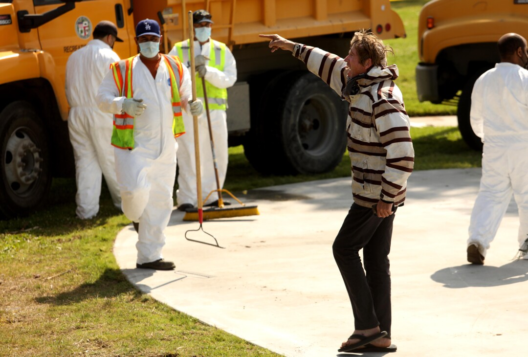 A homeless man yells at a sanitation crew workers in white jumpsuits