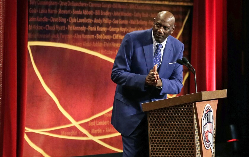 Spencer Haywood thanks Charles Barkley, pictured above him on a screen, at the 2015 Basketball Hall of Fame ceremony.