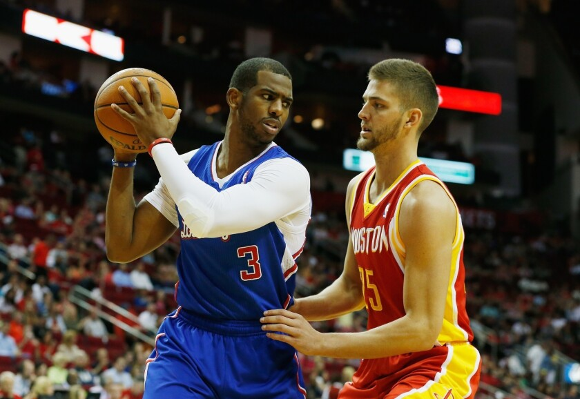 Clippers point guard Chris Paul, left, tries to work his way past Houston Rockets small forward Chandler Parsons during the first half of the Clippers' 118-107 win Saturday. The Lakers play the Clippers for the final time this season Sunday.