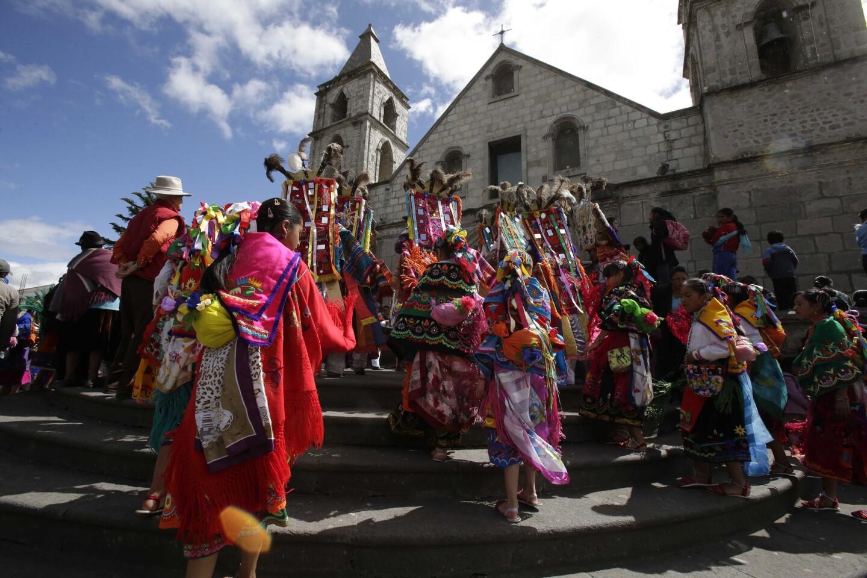 Un grupo de danzantes entra en la iglesia al comienzo de las fiestas del Corpus Christi en Pujilí, Ecuador. El sacerdote permite la entrada a los bailarines, que después actúan en honor del Dios cristiano.