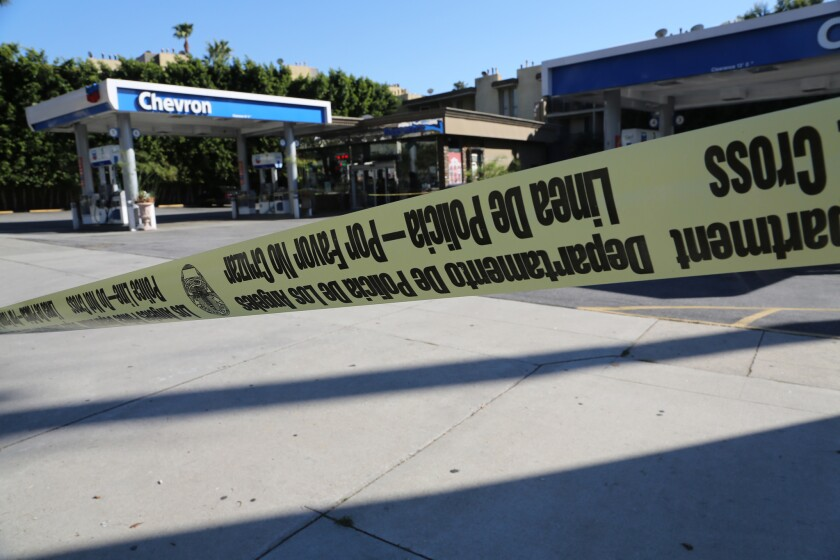 Crime scene tape wraps around the Chevron station mini-mart where a clerk was shot to death during a Jan. 17 robbery.