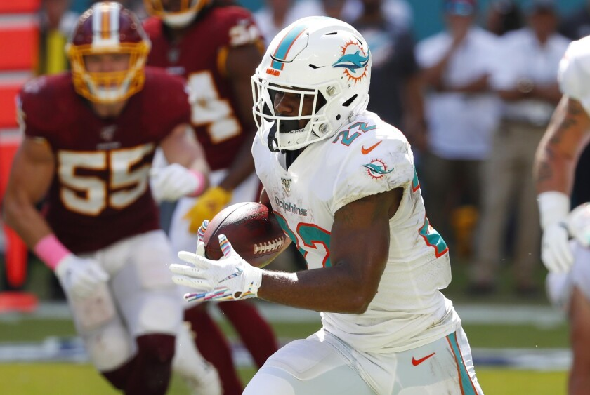 FILE - In this Oct. 13, 2019, file photo, Miami Dolphins running back Mark Walton (22) runs with the football during the first half at an NFL football game against the Washington Redskins in Miami Gardens, Fla. Walton has been suspended without pay for the next four games for violating NFL conduct and substance abuse policies. (AP Photo/Wilfredo Lee, File)