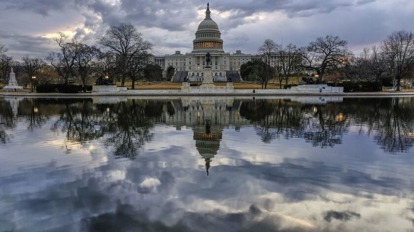 Clouds are reflected in the U.S. Capitol reflecting pool at daybreak in Washington as Day Three of t