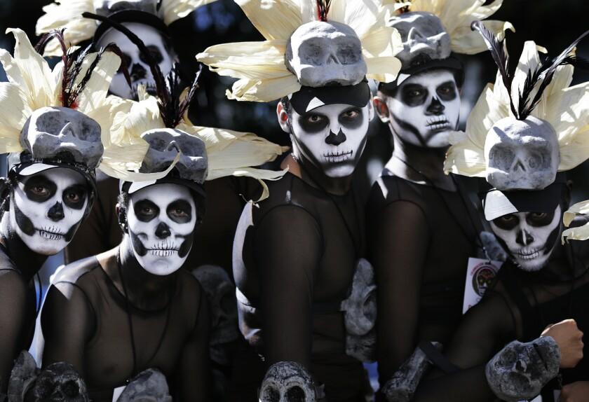 """Numerosos hombres con disfraces aguardan el inicio del primer desfile del Día de los Muertos por la avenida Reforma, una de las principales en la Ciudad de México, el sábado 29 de octubre de 2016. Las actividades tradicionales en torno al Día de Muertos en México, a decir reuniones tranquilas de familias en las tumbas de sus difuntos, están cambiando rápidamente ante la influencia de las películas de Hollywood, programas de zombis, el Halloween (Día de las Brujas) e incluso la politica. La Ciudad de México efectuó su primer desfile del Día de los Muertos, una idea salida de la imaginación del guionista de la cinta """"Spectre"""" de James Bond que se estrenó el año pasado. En la película, cuyas primeras escenas fueron filmadas en la Ciudad de México, Bond persigue a un villano entre muchedumbres que parecen participar en un desfile en el que se desplazan carrozas alegóricas y personas usan disfraces de esqueletos. (AP Foto/Marco Ugarte)"""