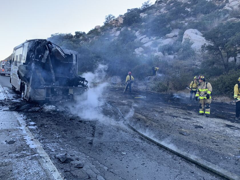 Firefighters mop up a blaze that spread Tuesday afternoon from an RV to the vegetation on the side of south I-15 near Rainbow