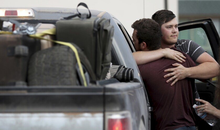 Cole Langford, left, and Hayden Spenct of the Mormon colony in La Mora, Mexico, hug at a gas station Nov. 9 in Douglas, Ariz. Members of the colony began leaving Mexico this weekend.