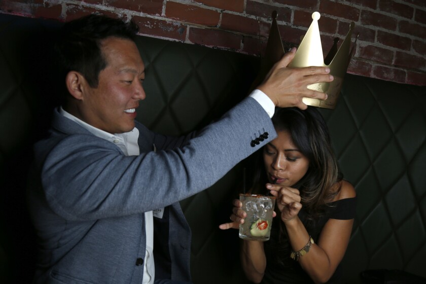Jason attempts to crown Megan with their punch bowl drink during their dinner at the Monkey King restaurant in downtown San Diego.