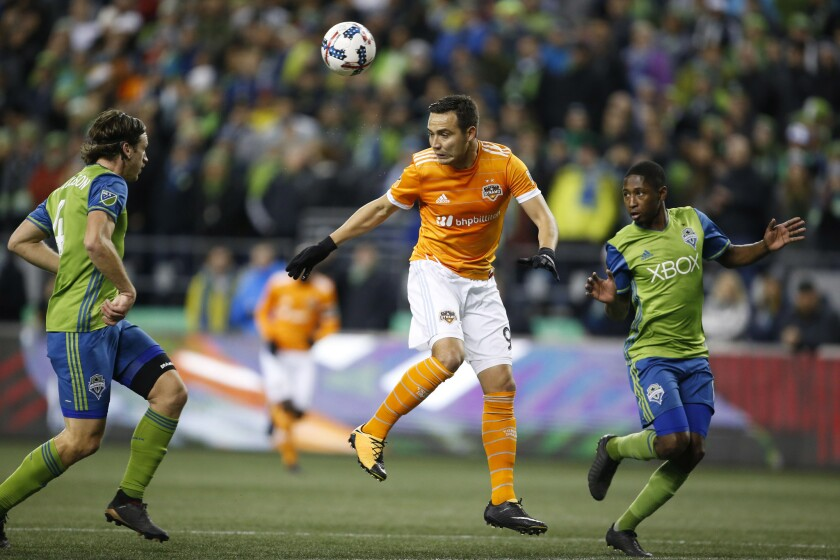 Nov 30, 2017; Seattle, WA, USA; Houston Dynamo forward Erick Torres (9) heads the ball in-between Seattle Sounders FC defender Gustav Svensson (4) and defender Kelvin Leerdam (18) during the second half in the second leg of the Western Conference championship at CenturyLink Field.