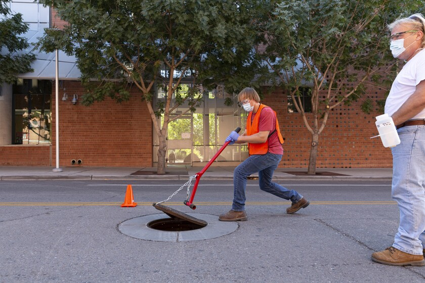 A student opens a manhole cover on a street.