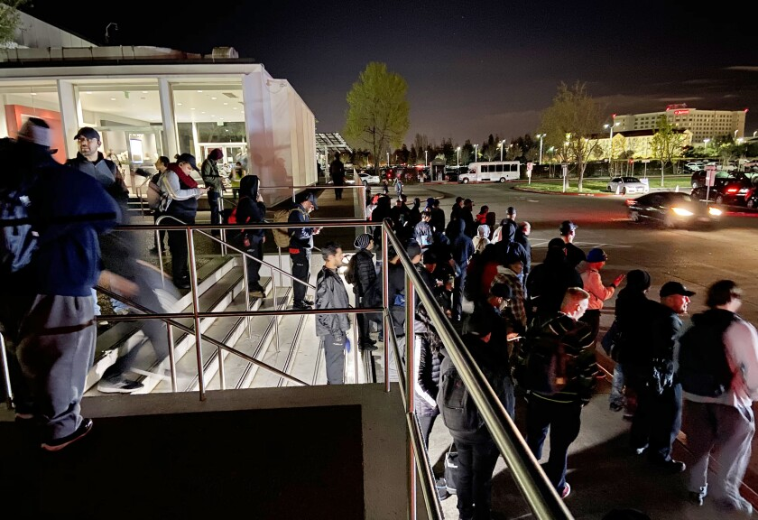 Tesla workers coming off the night shift wait to board buses at the Fremont factory March 17.
