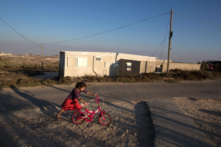 An Israeli girl walks with her bicycle near her home in the Amona settlement, northeast of the Palestinian city of Ramallah in the Israeli occupied West Bank on Sept. 7, 2016.