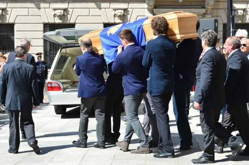 The coffin of designer Ottavio Missoni is carried by pallbearers from the Santa Maria Assunta Church in Gallarate, Itlay, on Monday.
