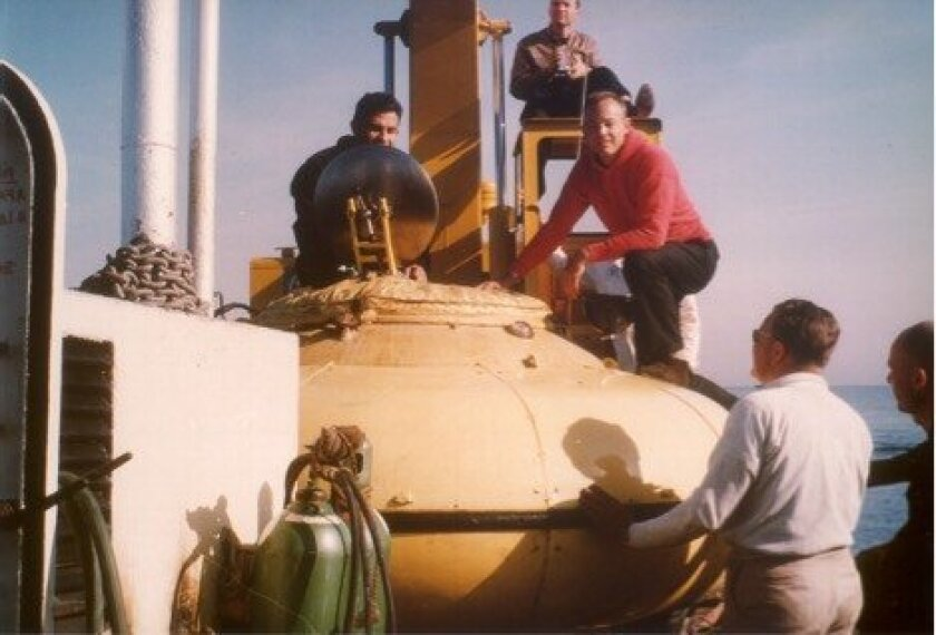 "Doug Inman (red shirt) stands on top of Cousteau's ""Diving Saucer"" in 1964."